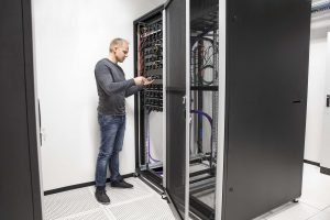 IT engineer or technician working with network cabling and installation communication switches in datacenter.